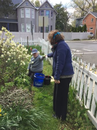A HAP volunteer presents a cloth face mask to a senior who is gardening.